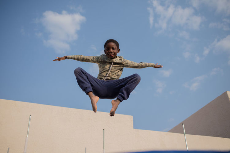 Low angle portrait of boy with arms outstretched jumping against sky