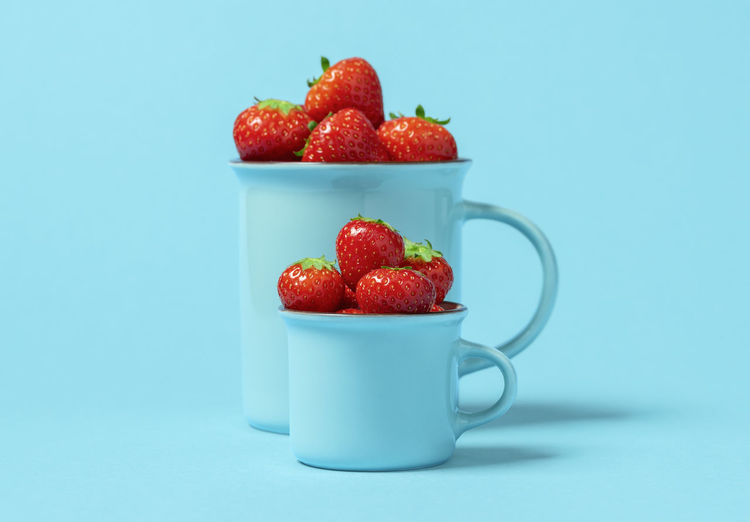 Close-up of strawberries and fruit on table against blue background