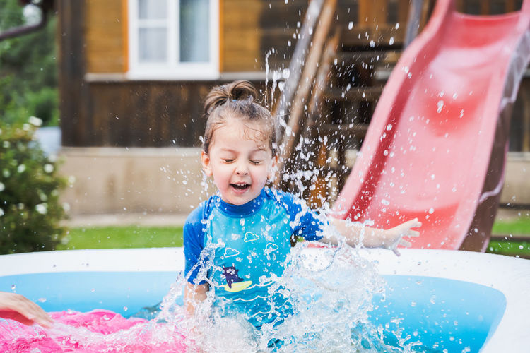Girl playing in inflatable tub