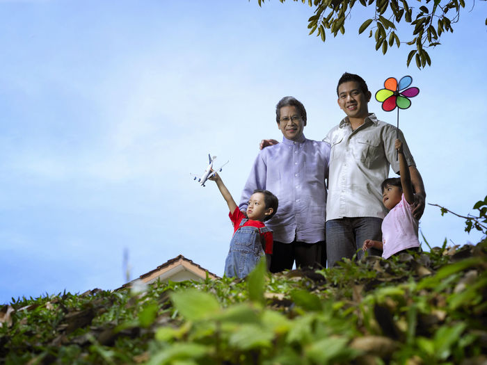Low angle view of family standing against sky