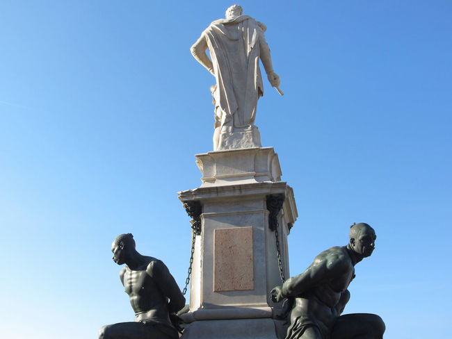 The monument Quattro Mori ( of the Four Moors ) in Livorno city . Rear view of the monument against the blue sky . Tuscany, Italy African ArtWork Bandini Bronze Four Livorno Medici Renaissance Square Statue Tacca Tuscany Art Black Chain Historic Italy Monument Moorish Moors Mori Muscle Sculpture Slave Tourism