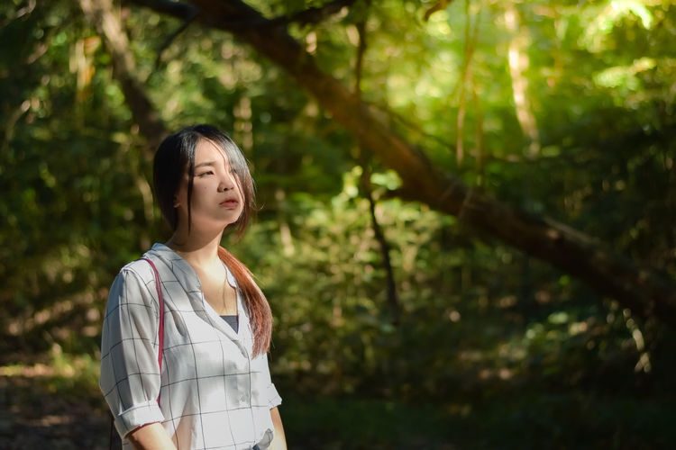 Thoughtful woman standing in forest