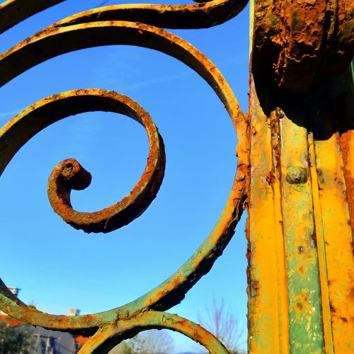 Low angle view of rusty gate detail against clear blue sky