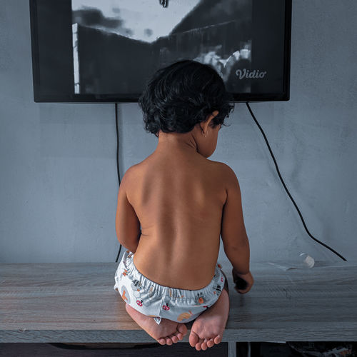 Rear view of shirtless boy standing against wall