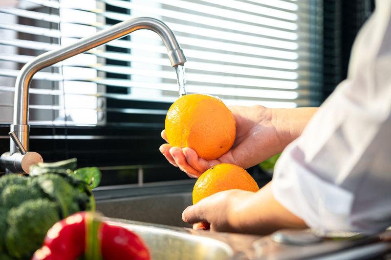Cropped image of hand holding orange fruit