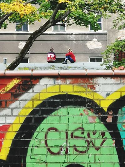 People standing by graffiti on wall