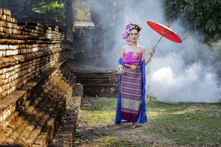 Woman holding umbrella standing against built structure
