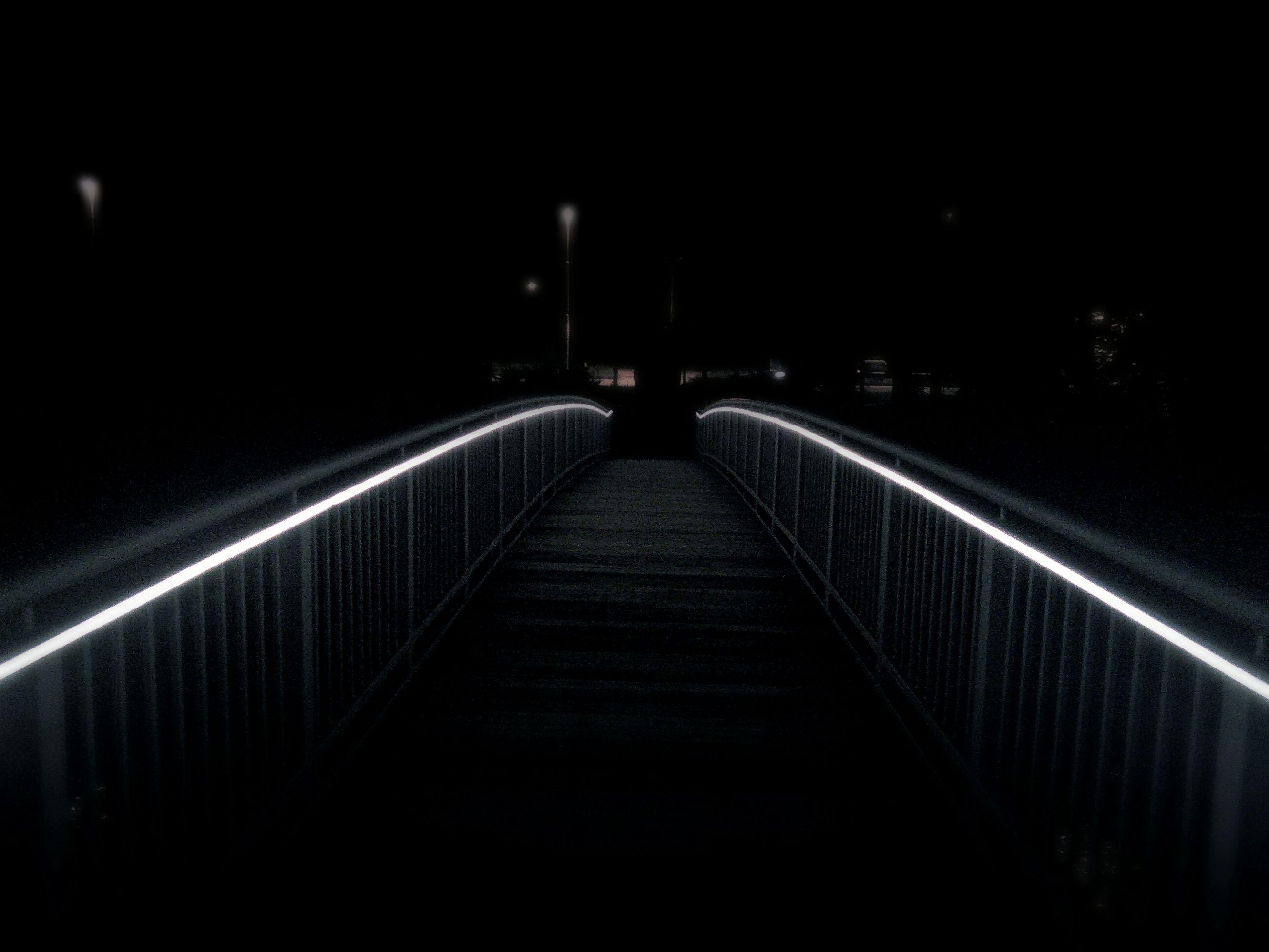 the way forward, night, railing, illuminated, connection, bridge - man made structure, diminishing perspective, footbridge, built structure, vanishing point, architecture, long, bridge, transportation, dark, narrow, walkway, outdoors, no people, street light
