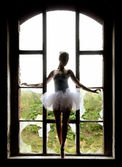 Full length of ballerina posing on broken window sill