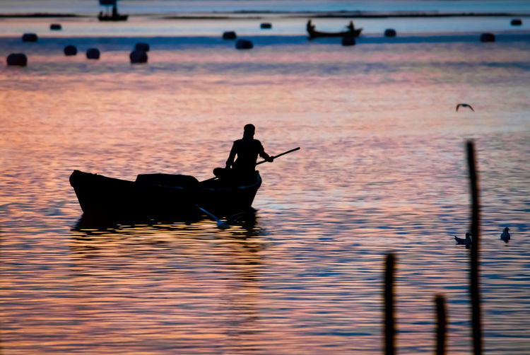 Sunset and silhouette of boatman at Triveni Sangam (confluence of three rivers), Kumbh Mela festival, Allahabad known as Prayagraj, Uttar Pradesh, India. Water Silhouette Waterfront Nature Reflection Beauty In Nature Sunset Outdoors Scenics - Nature India Uttar Pradesh Kumbh Mela Boat Boatman Festival Allahabad Ganga Yamuna Saraswati Holy Ceremony Hinduism Triveni Sangam Confluence River
