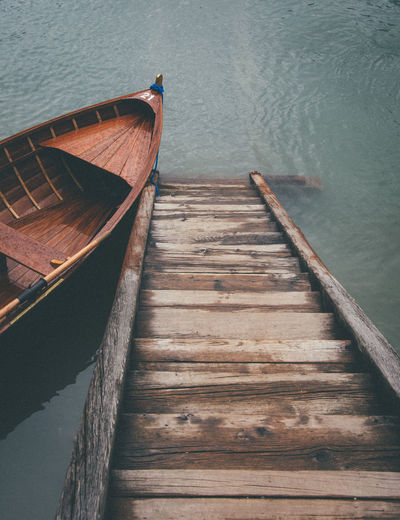 High angle view of rowboat by wooden steps in lake