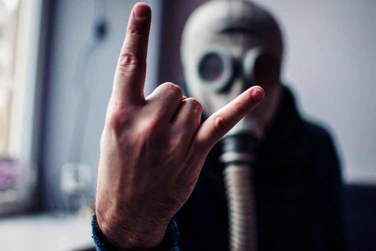 Close-up of man showing horn sign while wearing gas mask