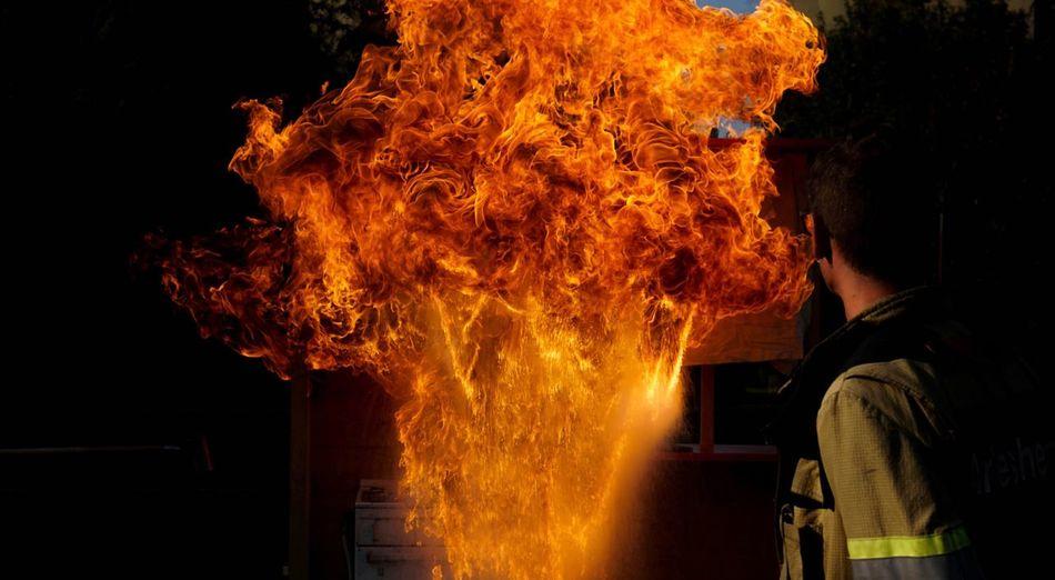 Firefighter standing against fire