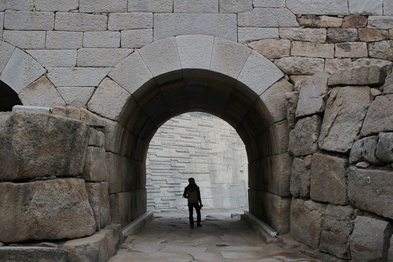 Rear view of man walking against wall