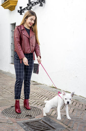 Happy young woman standing with dog on footpath