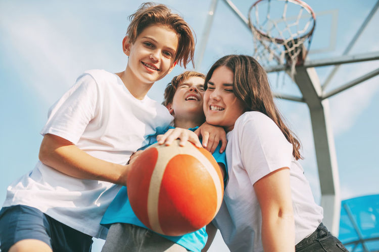 Low angle view of cheerful siblings playing with basketball against sky