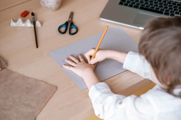 High angle view of woman holding paper with pencils on table