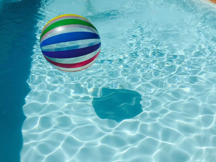 High angle view of stripped balll on rippled water in swimming pool