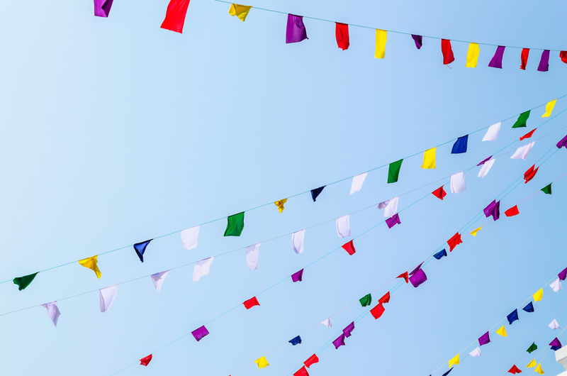 Sky Multi Colored Low Angle View Decoration Flag Hanging Celebration Bunting Clear Sky Blue Large Group Of Objects No People Nature Day Side By Side Wind Outdoors String Streamer