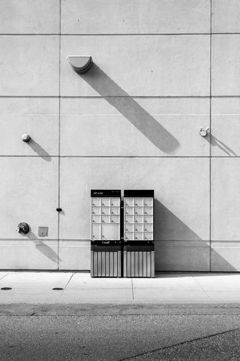 A black and white photograph of canadian mailboxes in a deserted big box retail shopping zone.