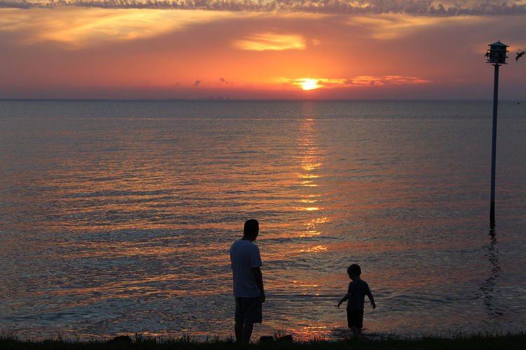 Father and son enjoying a special moment. Beach Calm Enjoyment Escapism Getting Away From It All Hobbies Horizon Over Water Idyllic Light Outdoors Reflection Rippled Scenics Sea Shore Tranquil Scene Vacations Water Waterfront Weekend Activities Father And Child Son And Dad Playing In Bay As Sunsets On Horizon