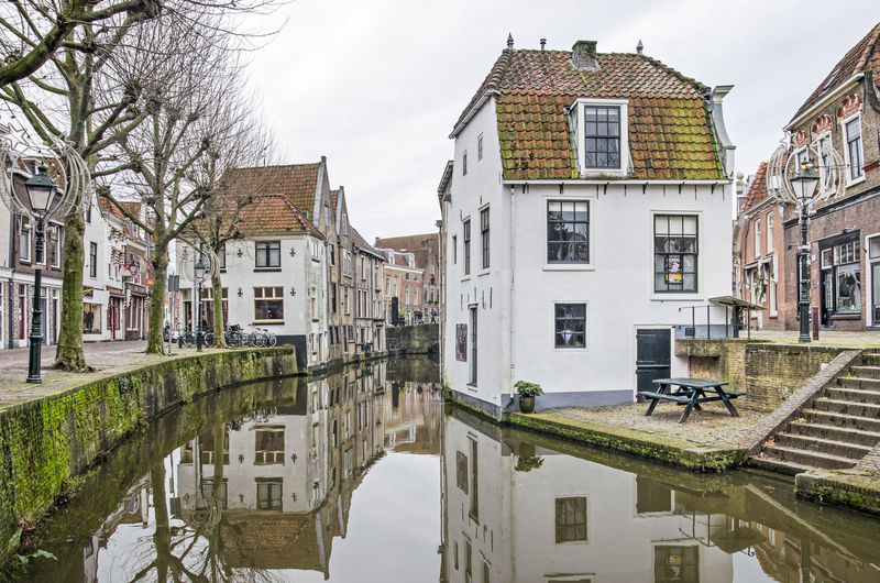Canal amidst buildings in town against sky
