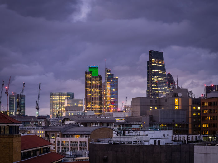 Illuminated buildings in city against sky at dusk