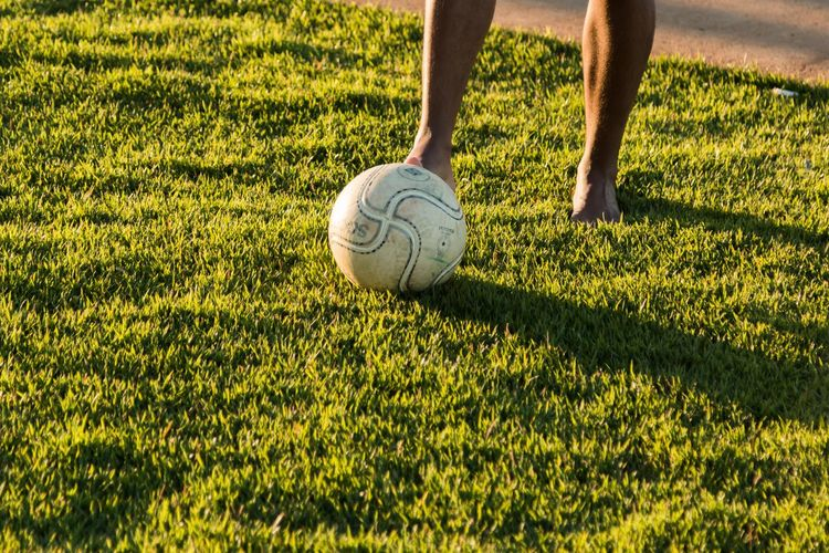 Low Section Of Man Playing Soccer On Field During Sunny Day