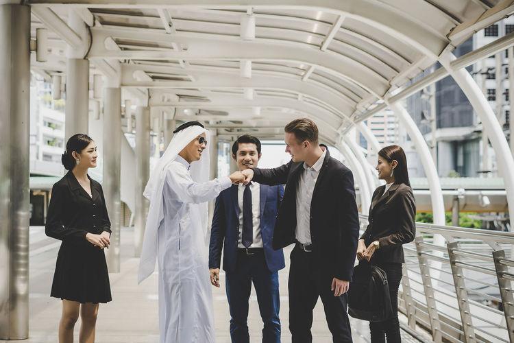 Business people standing on footbridge in city
