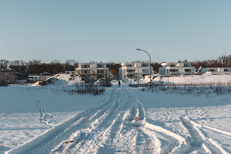 Snow covered houses by buildings against clear sky