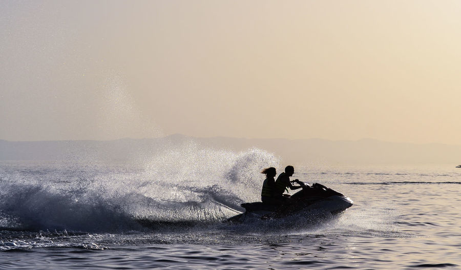 Couple riding jet boat on sea against clear sky