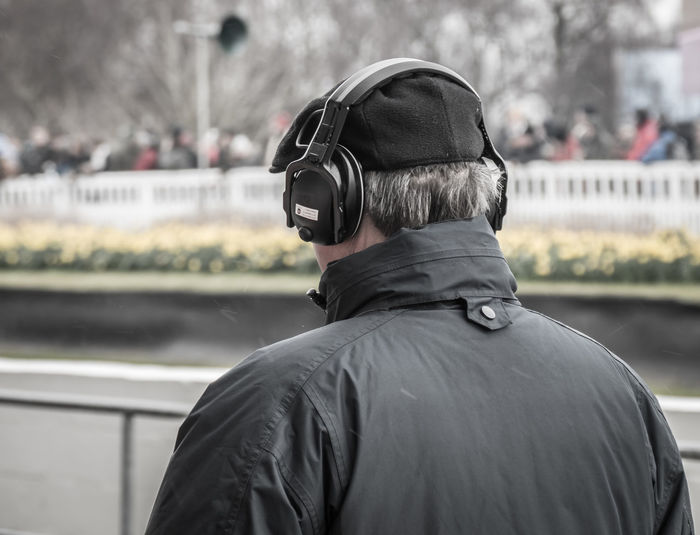 Rear view of man listening music in city