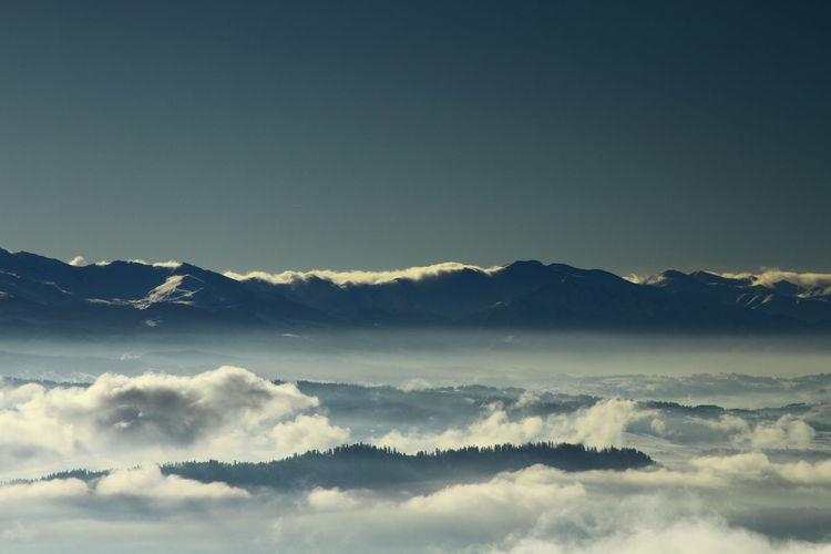 Scenic view of cloud covered mountains against clear sky at dusk