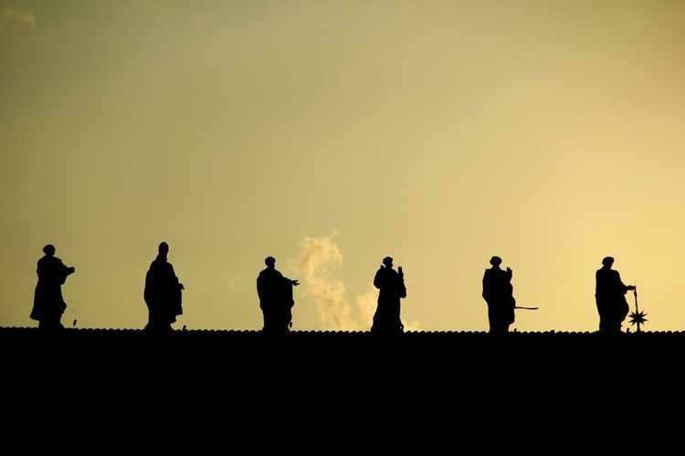 Silhouette statues against the sky