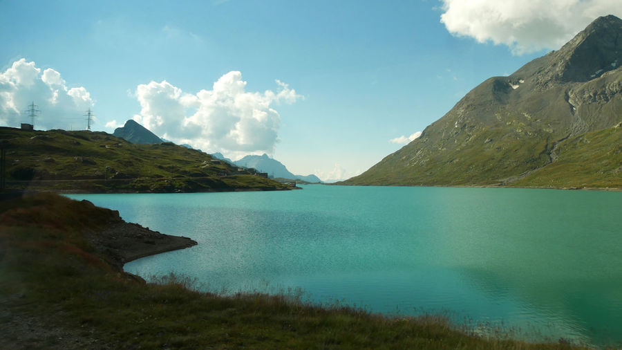 High alpine lake in the swiss alps Water Sky Mountain Cloud - Sky Scenics - Nature Beauty In Nature Tranquility Tranquil Scene Nature Landscape Environment No People Sea Day Non-urban Scene Idyllic Land Beach Outdoors Range