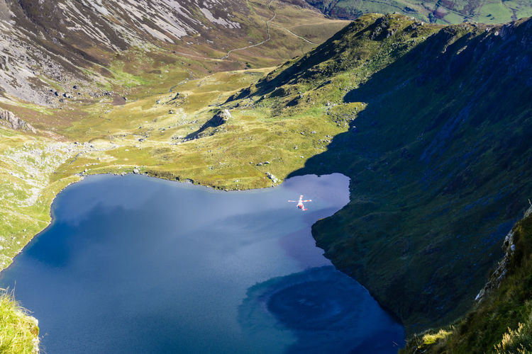 Aerial View Of Rescue Helicopter Flying Over Lake At Snowdonia National Park