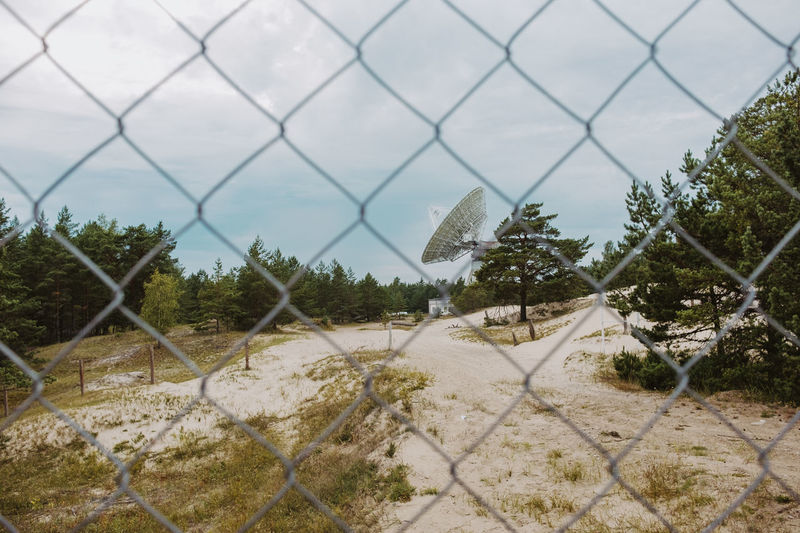 Panoramic view of landscape seen through chainlink fence