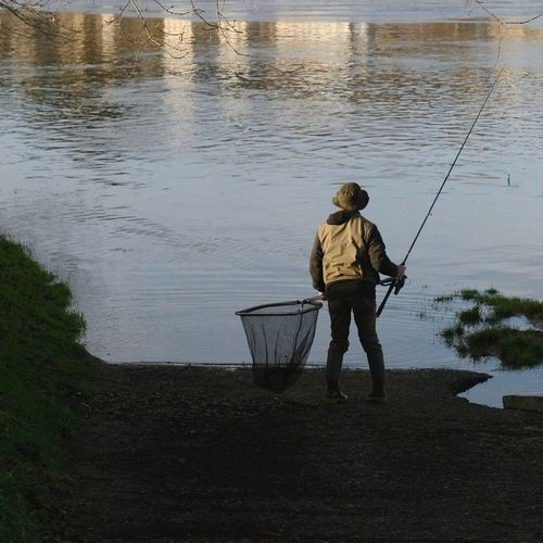 Rear View Of Man Fishing In Lake