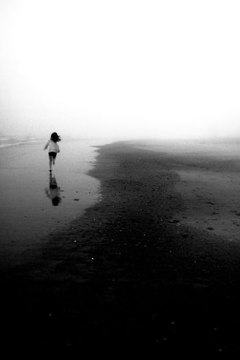 Rear view of woman running at beach during foggy weather