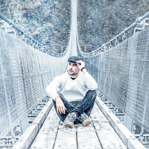 Full Length Of Man Sitting On Footbridge During Snowfall