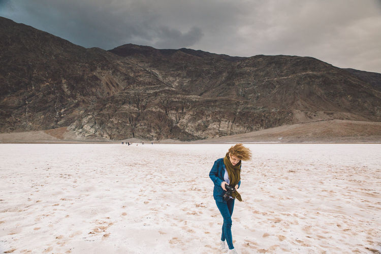 Young woman holding camera walking at death valley national park against sky