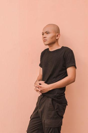 Man looking away against orange wall