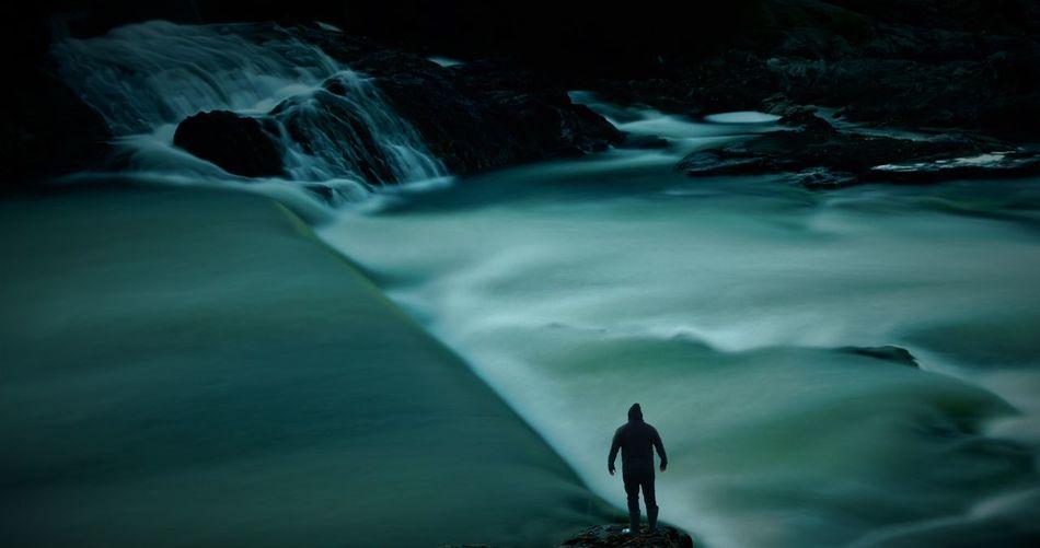 Man surfing on rock in sea