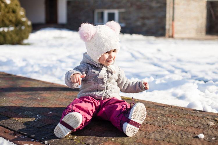 Full length of baby girl sitting on snow