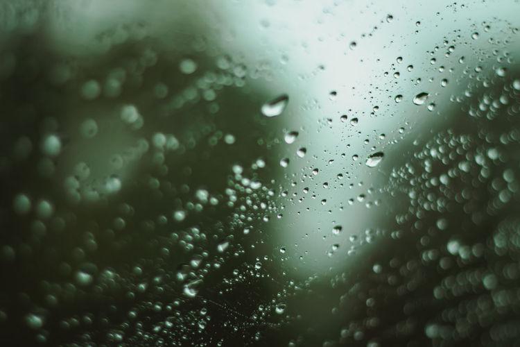 Melancholic full frame shot of raindrops on glass window