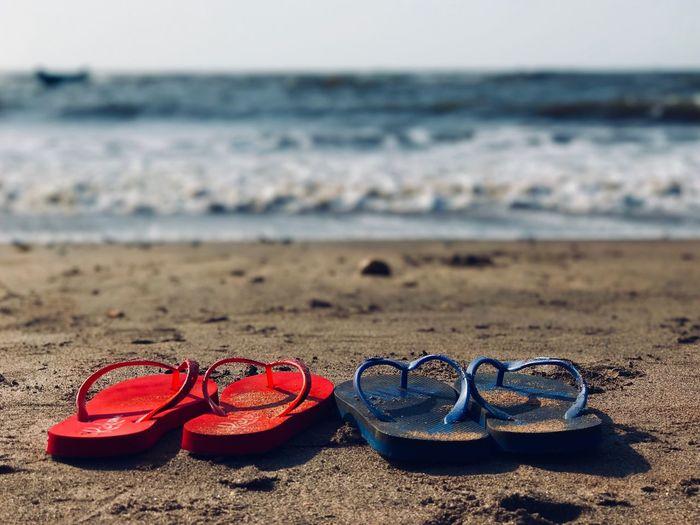 Close-up of flip-flops at beach