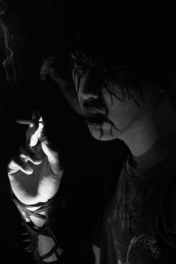 Close-up of young man with spooky face paint smoking in darkroom