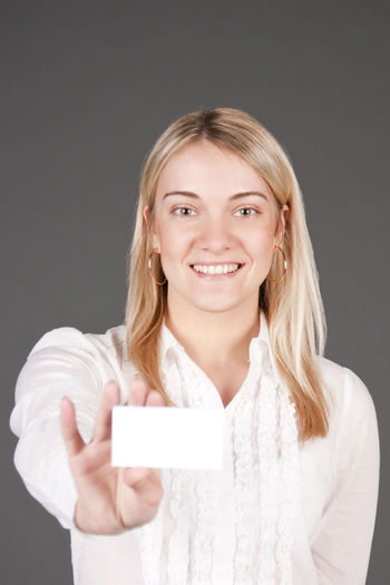 Portrait Of Smiling Businesswoman Holding Card Against Black Background