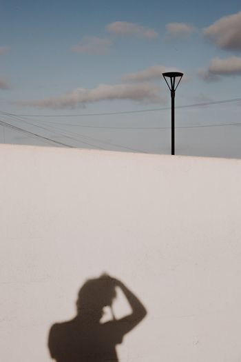 Shadow of person on street light against sky
