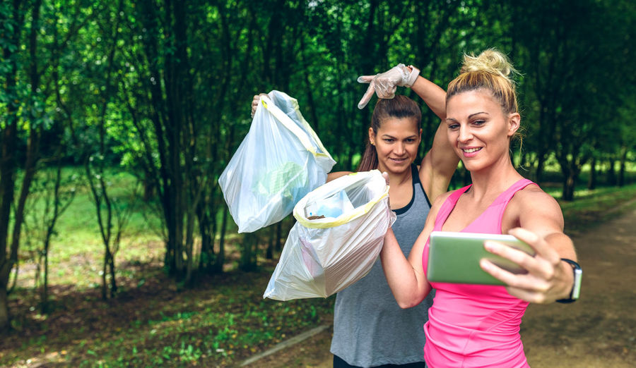 Smiling women taking selfie on smart phone while holding garbage